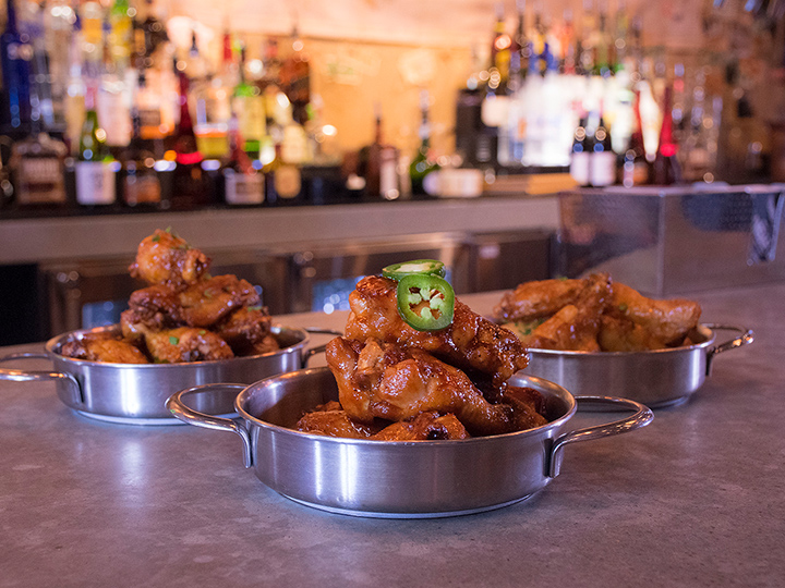 Three serving pans of Wu Han's Hot Wings on a bar counter at Jock Lindsey's Hangar Bar