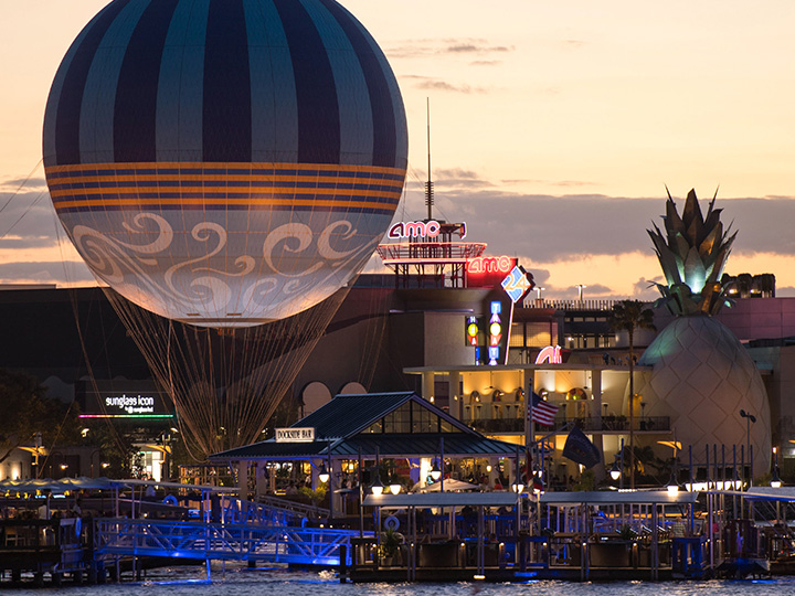 The world's largest tethered helium balloon positioned at its docking station within Disney Springs West Side at dusk