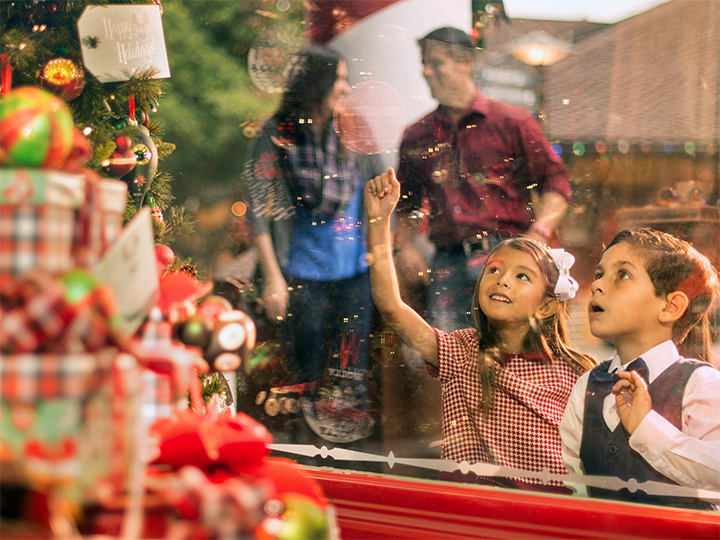 Two young children look in awe at a decorated Christmas tree on display in a shop window at Disney Springs
