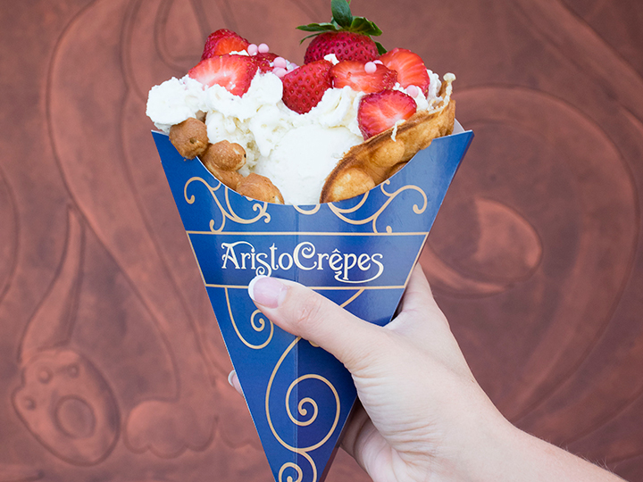 A bubble waffle in an Aristocrepes wrapper is filled with vanilla ice cream, strawberries and whipped cream