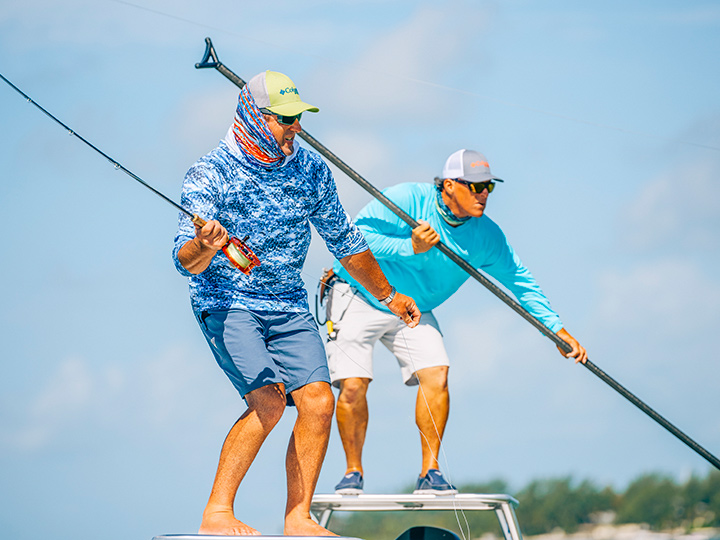 Two men wearing attire and gear from Columbia Sportswear attempt to reel in a fish as they stand side by side on a boat