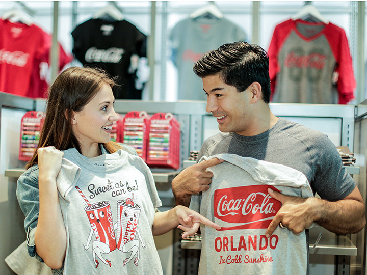 A young couple hold up Coca Cola graphic T shirts inside the Coca Store at Disney Springs