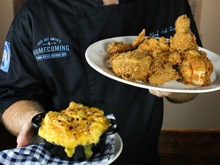 A server from Chef Art Smith's Homecoming presents a plate of fried chicken and a mini casserole dish of mac and cheese