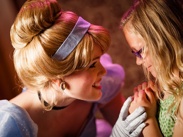 Cinderella leans in close to a little girl and smiles