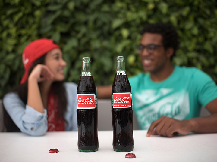 Two Coca Cola bottles with the caps off, rest on a table in front of 2 friends