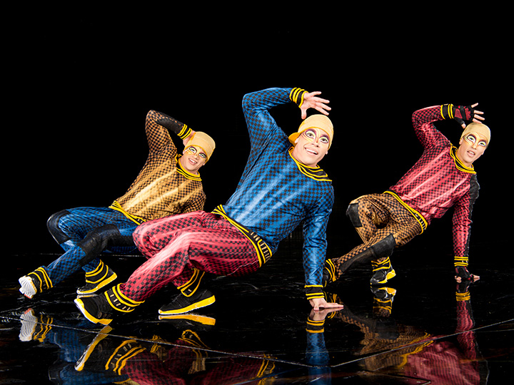 Three male break dancers, with their faces painted, perform on stage during a La Nouba by Cirque du Soleil show