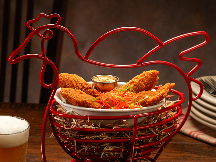 Chicken tenders inside a wire basket shaped like a chicken next to a glass of beer