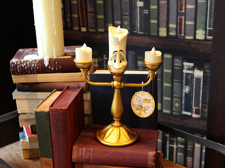 A Lumiere light up figurine displayed on a cart of old books at D Living, a home décor boutique within Disney Springs