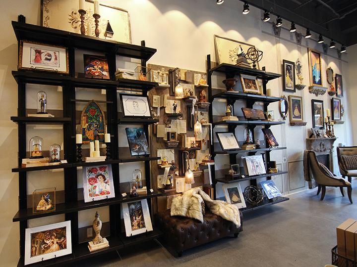 Shelves showcasing Beauty and the Beast themed prints and figurines within D Living at Disney Springs