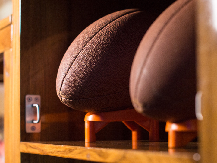 A duo of footballs resting within the top section of a locker-room cubby