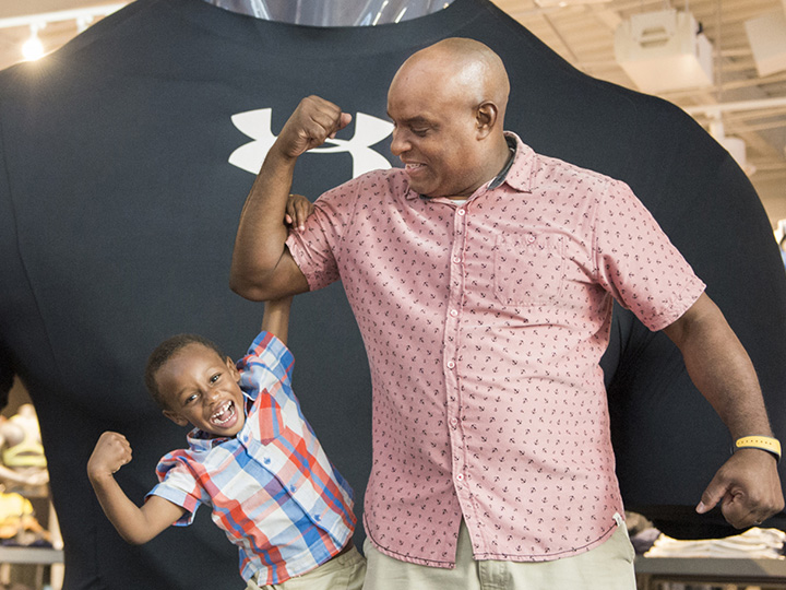 A young boy makes a muscle as he hands off his father's bicep in front of an Under Armour display