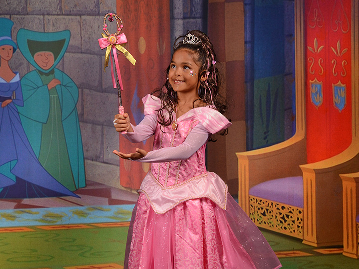 A young girl dressed as Aurora poses against a Sleeping Beauty themed digital backdrop