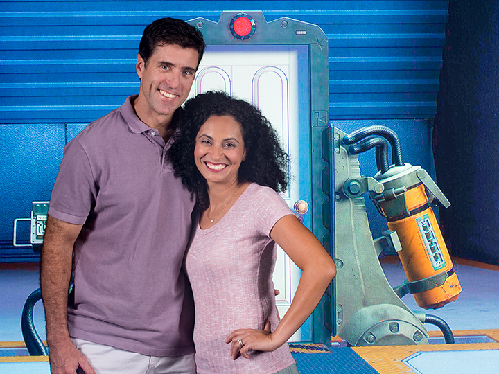 A couple stands in front of a futuristic backdrop
