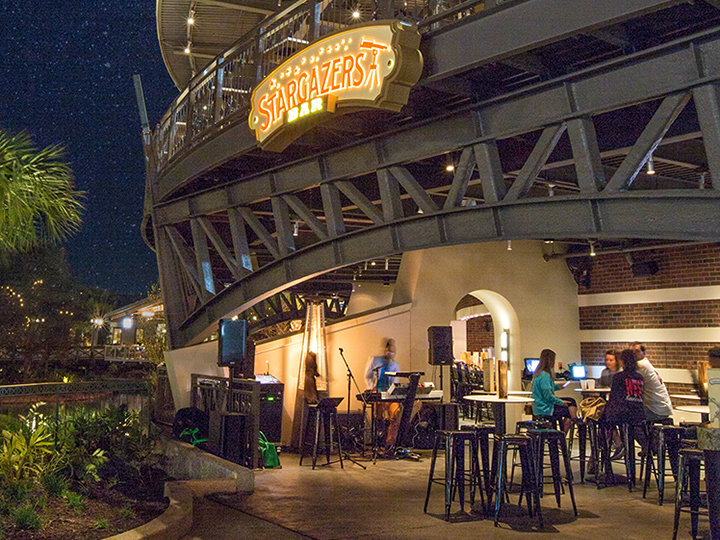 The patio of Stargazers Bar at night with a band setup and Guests seated at a bistro table