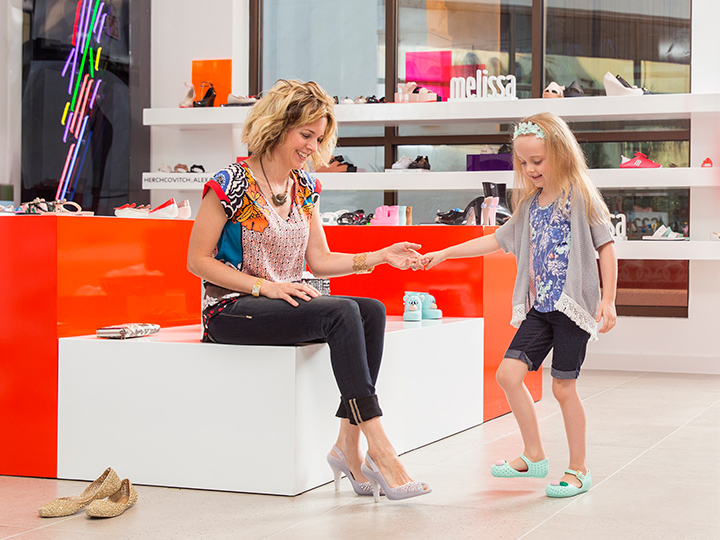 A woman sitting on a block tries on a pair of heels while holding her daughter's hand at Melissa Shoes