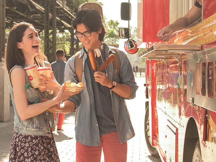 A laughing young woman carries multiple beverages and a carton of fries as her boyfriend holds 2 corn dogs and hands her a bottle of water