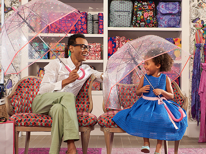 A father and his young daughter fit on accent chairs holding open see through umbrellas inside the Vera Bradley boutique.