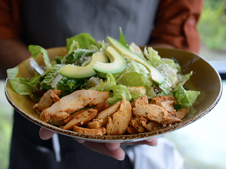 A plate of Caesar salad with chipotle chicken and avocado slices from Frontera Cocina at Disney Springs