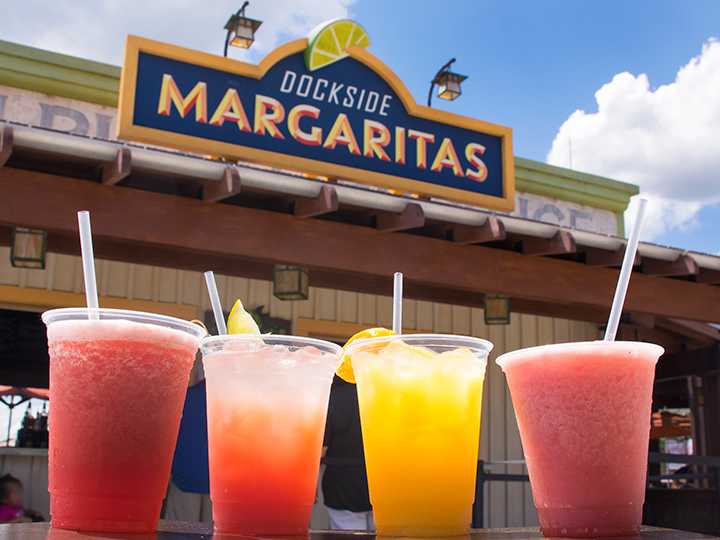A row of four frozen drinks on a table in front of the pickup window at Dockside Margaritas