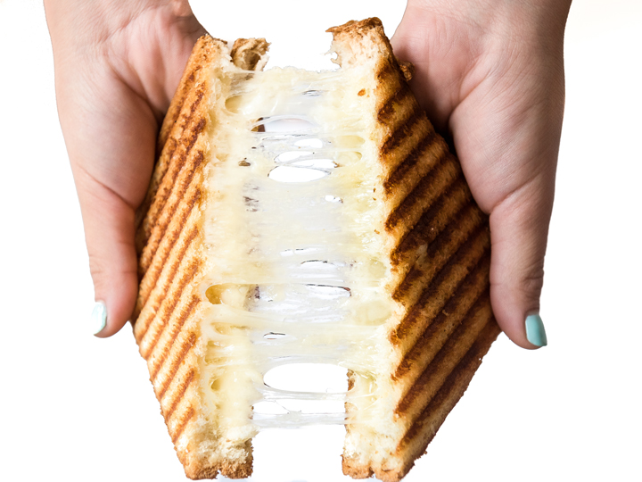 A web of cheese stretches between 2 grilled sandwich halves as they are broken apart