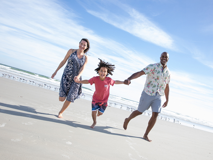 A couple running along the seashore with their young child