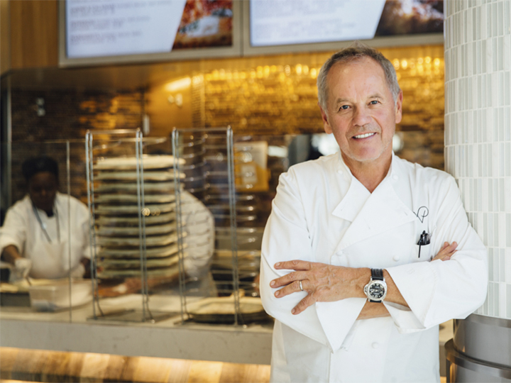 Wolfgang Puck posed in his restaurant, with chefs working at the counter in the background