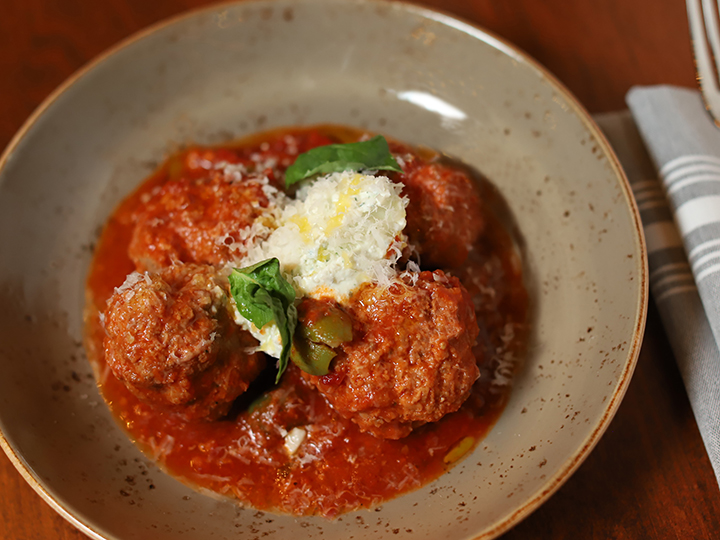 A serving of meatballs in tomato sauce garnished with grated cheese, basil and green olives