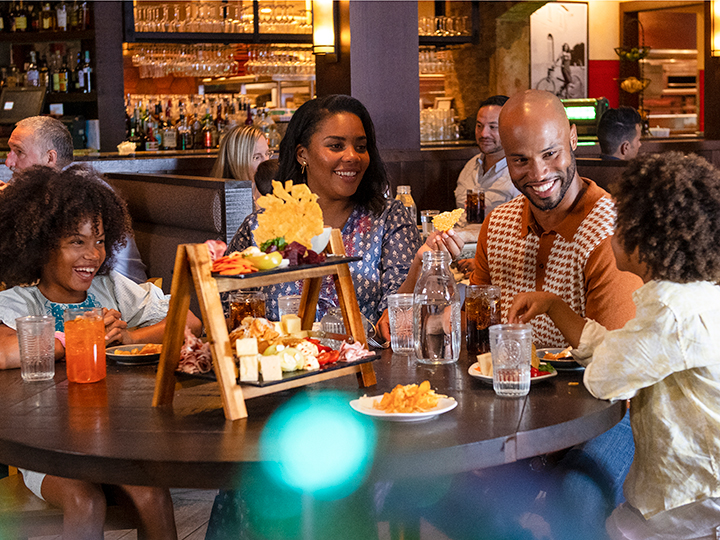 A family laughing around a dining table as they enjoy an assortment of appetizers