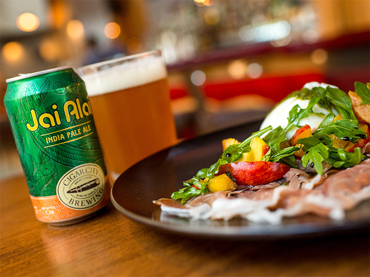 A plate of prosciutto and burrata cheese with arugula and sliced nectarines beside a can of beer poured into a glass