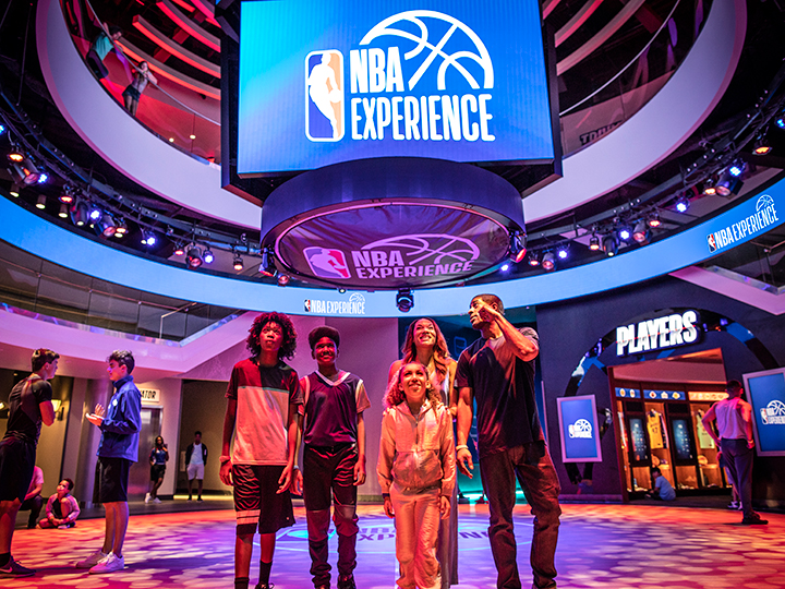 A smiling family of four exits the NBA Experience venue at Disney Springs