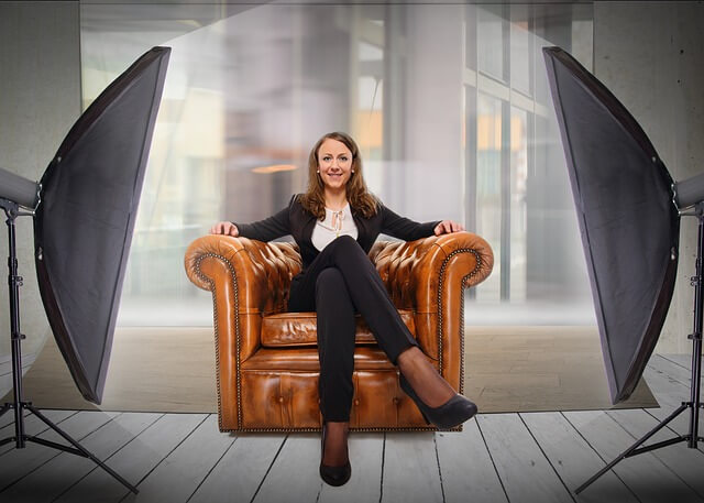 Woman sitting in a couch under spotlight