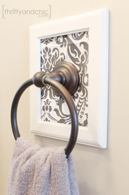 Framed towel holder provides extra decoration without taking up any space.