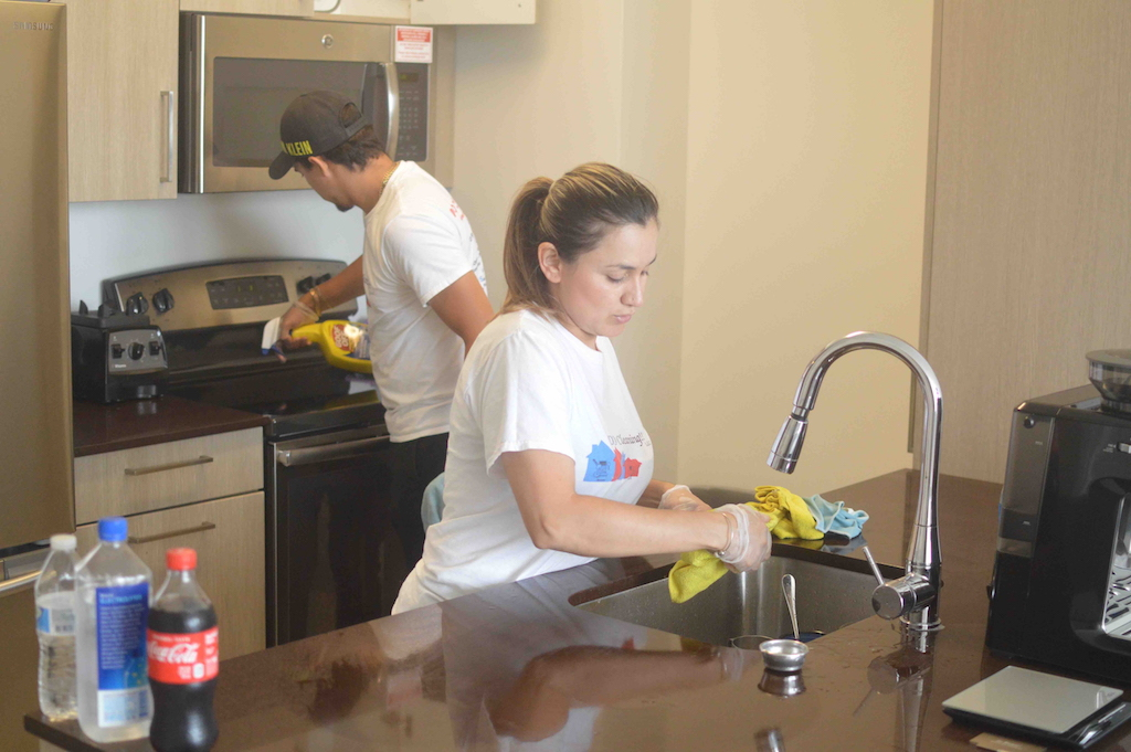 Owners Oscar and Diana cleaning a kitchen