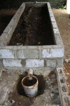 Figure 3: A concrete holding bin for vermiculture (this one at Earth University). The spout at the bottom allows leachate to escape. Photo by Danny Blank.