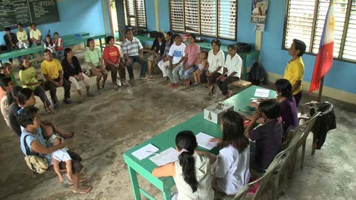 Figure 1: The start of a Savings Group meeting in the Philippines. The chairperson (standing) welcomes the group. Photos in this article are from World Vision, used with permission.