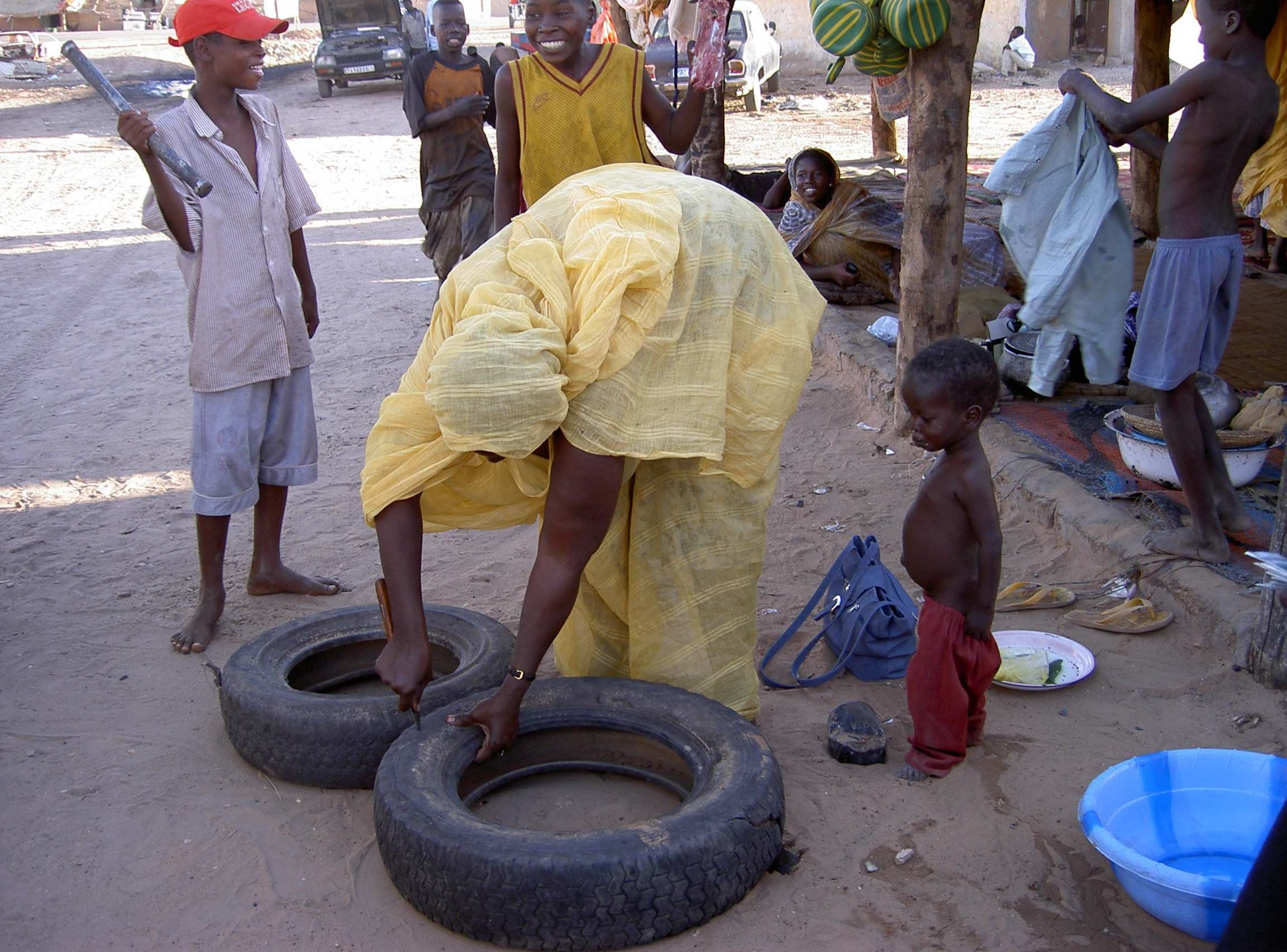 Figure 1: A woman making a moveable garden from an old tire.