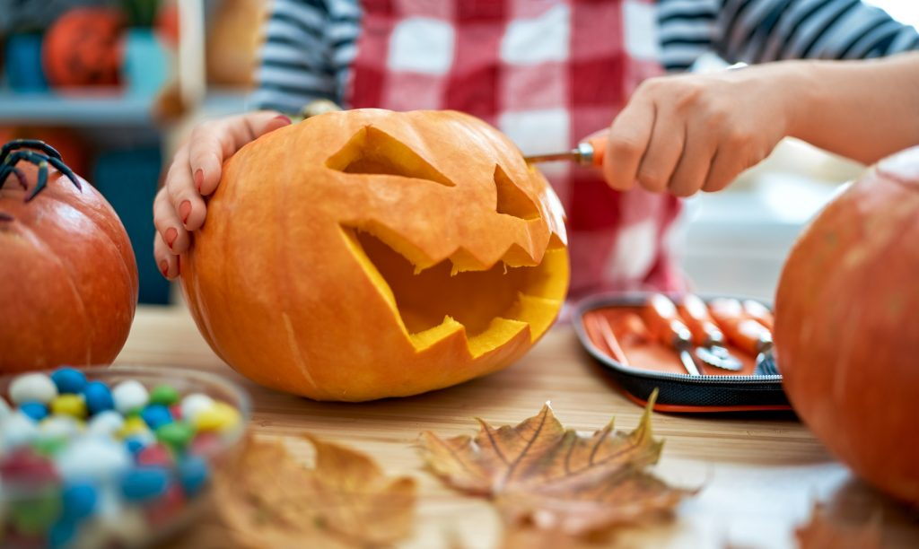 Woman is carving pumpkin