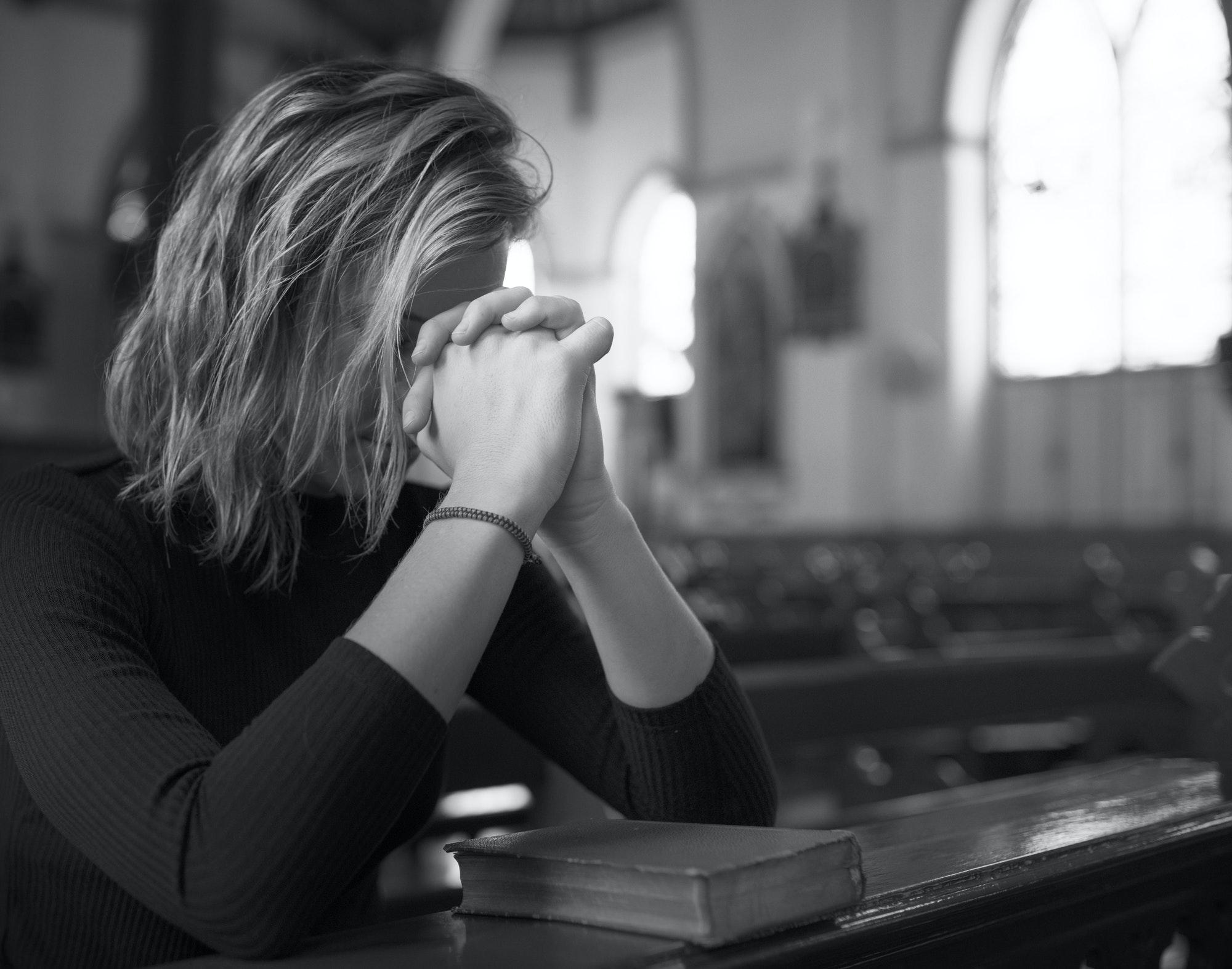 Woman praying in the church grayscale