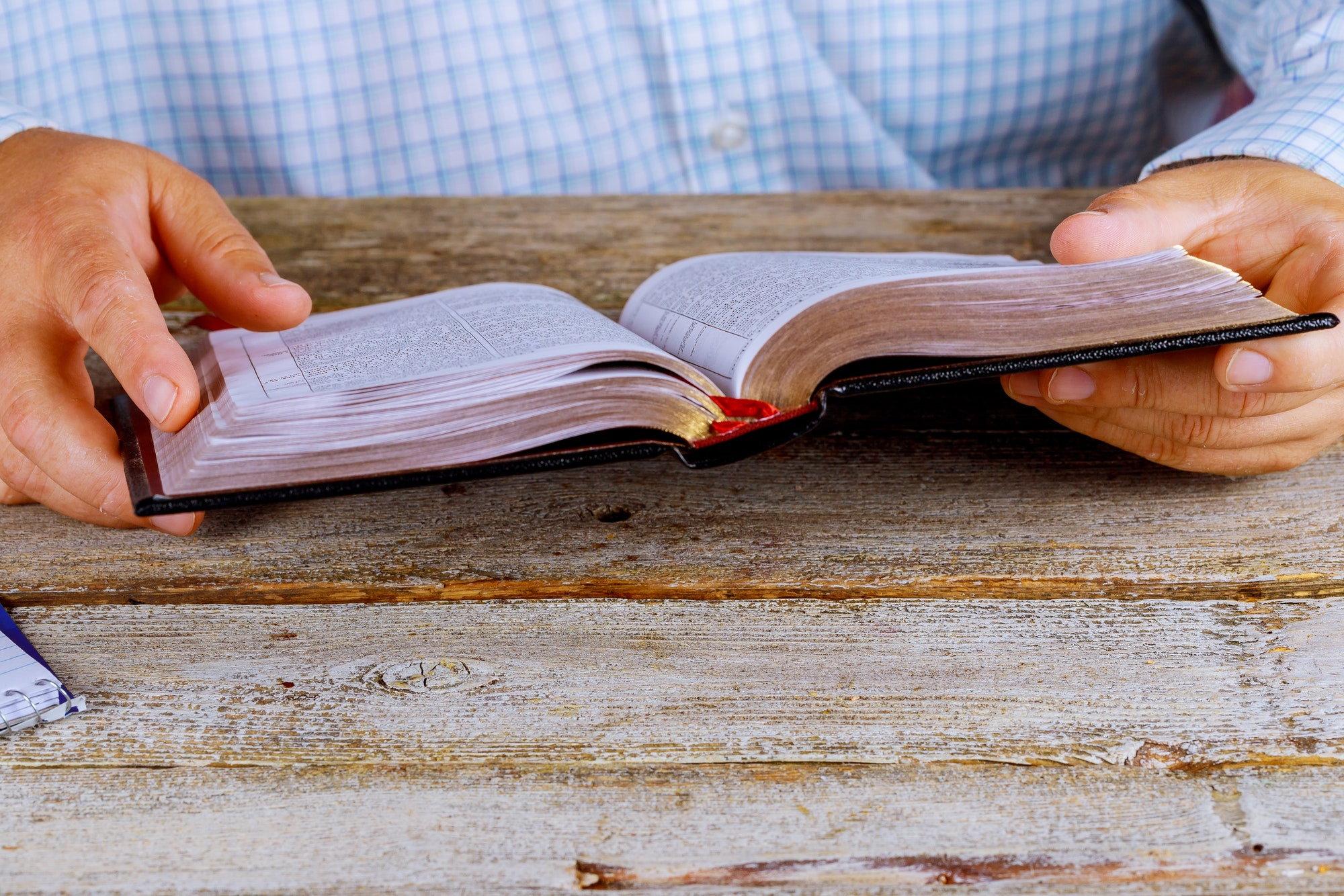 A men sitting reading the Holy Bible close up hands
