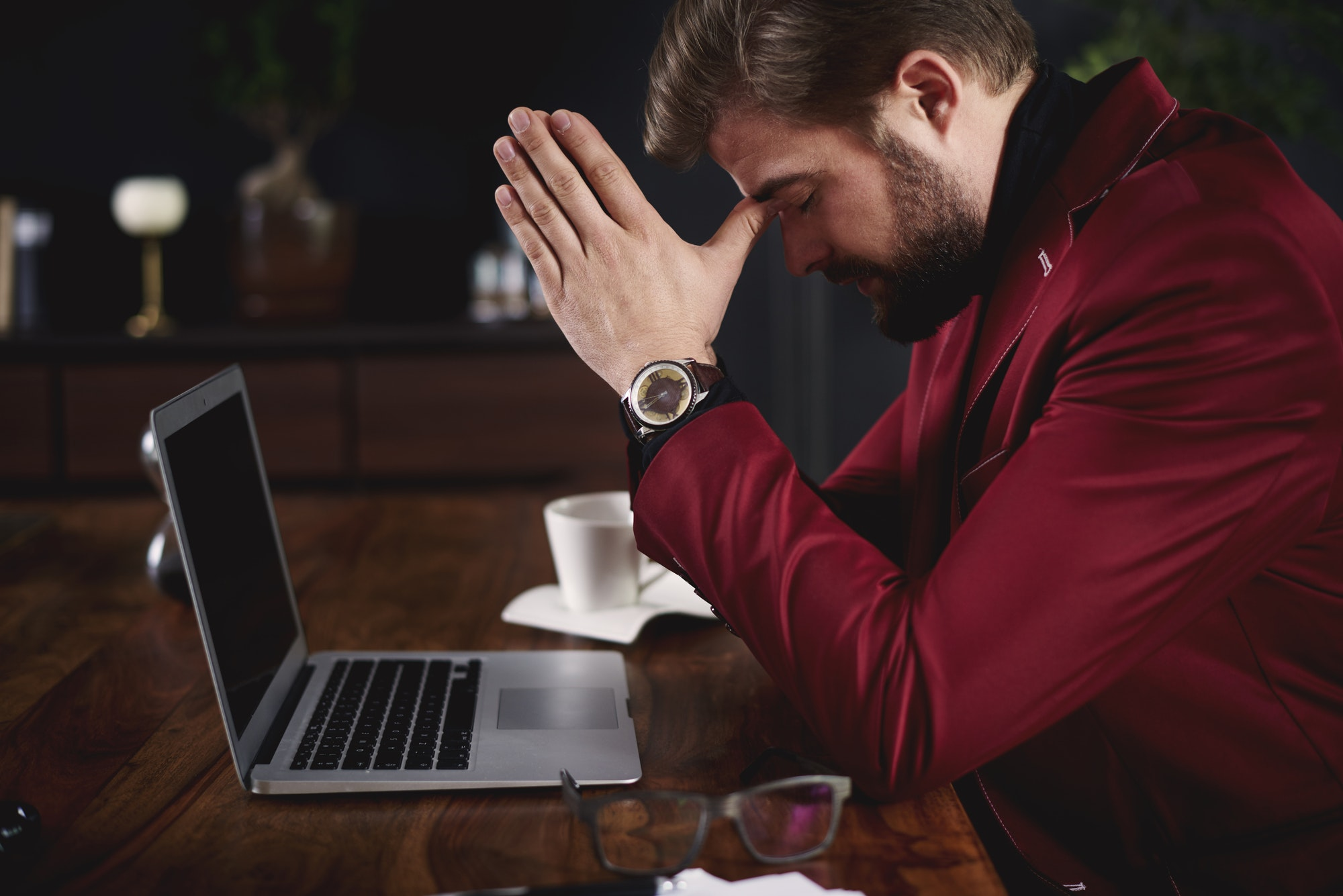 Worried businessman praying at his office