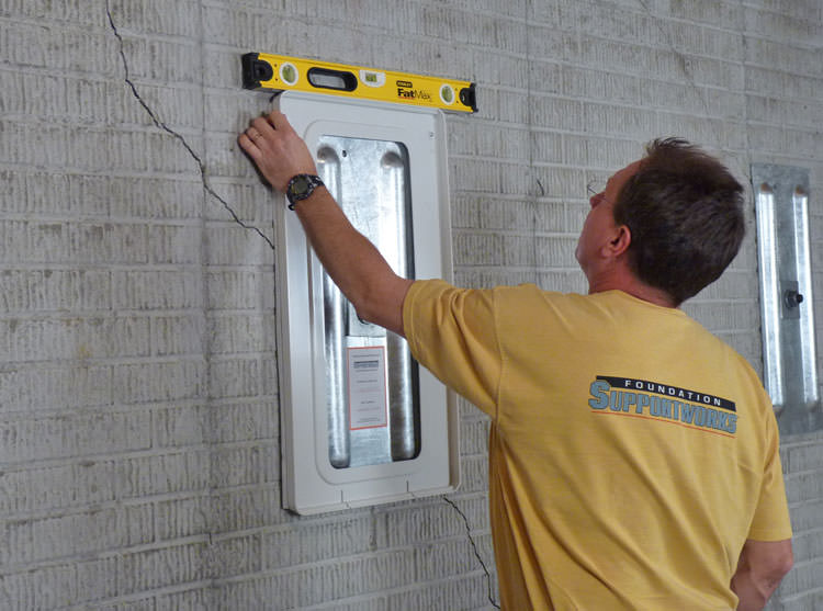 Positioning a wall plate cover on a foundation wall in Midland.