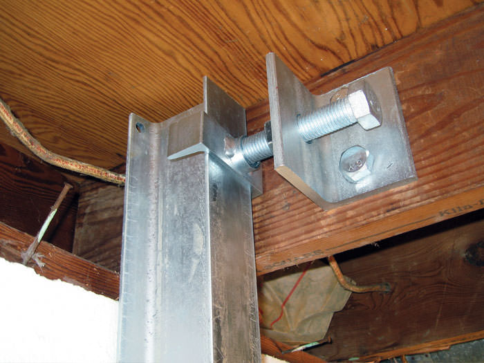 Securing the i-beam system to the top of the floor joist in a foundation wall repair in Traverse City.