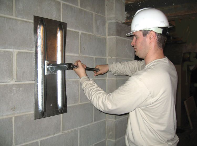 installing a wall anchor to repair an bowing foundation wall in Monroe