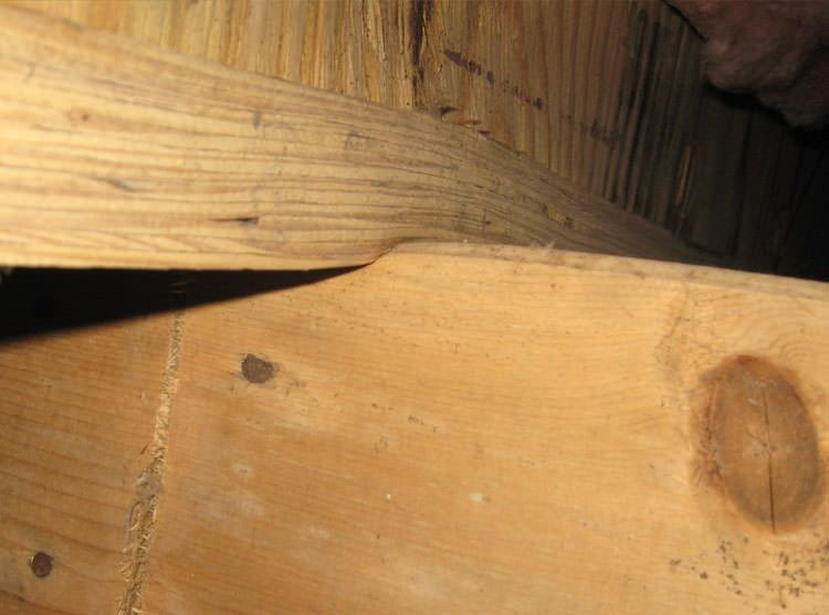 A failing girder showing signs of compression damage in a Michigan home