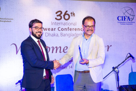 Men shaking hands during recognition for factoring services at International Footwear Conference