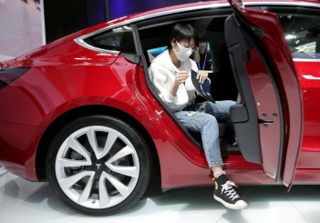FILE PHOTO: A woman sits in a Tesla Model 3 car during a media preview at the Auto China 2018 motor show in Beijing