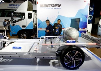 FILE PHOTO: Visitors looks at the frame of an electric vehicle next to a Foton autonomous truck at the stall of the BAIC Group automobile maker at the IEEV New Energy Vehicles Exhibition in Beijing