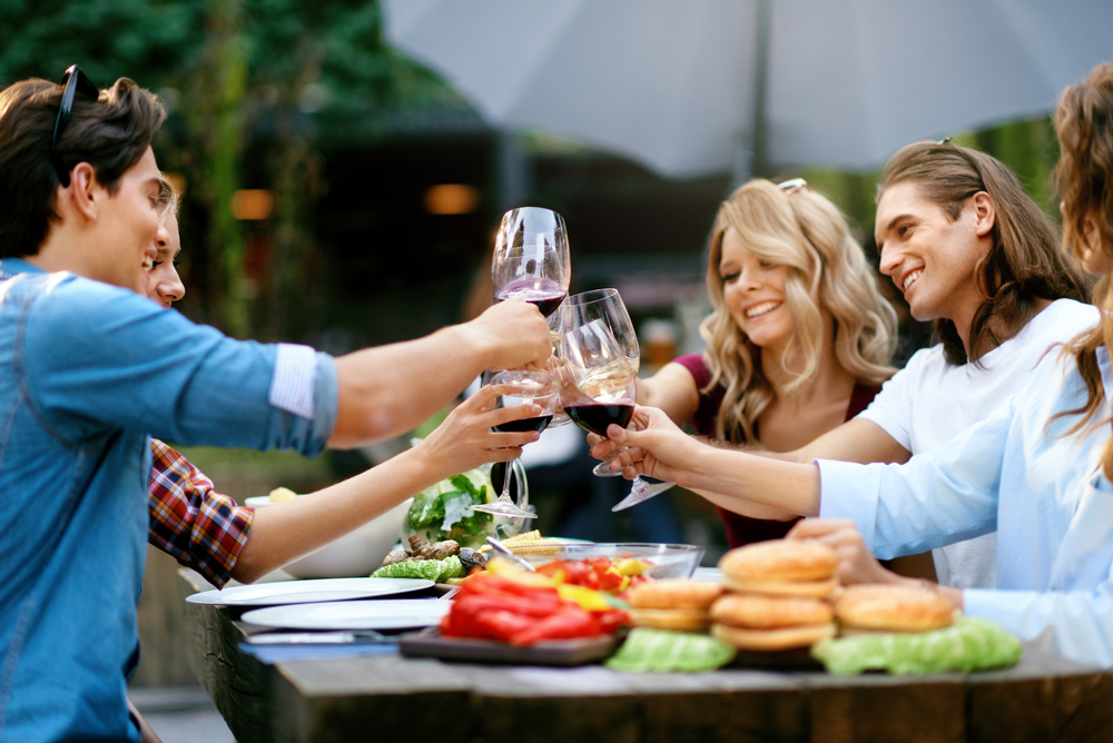 Friends Toasting With Drinks At Dinner Party Outdoors in Savannah GA