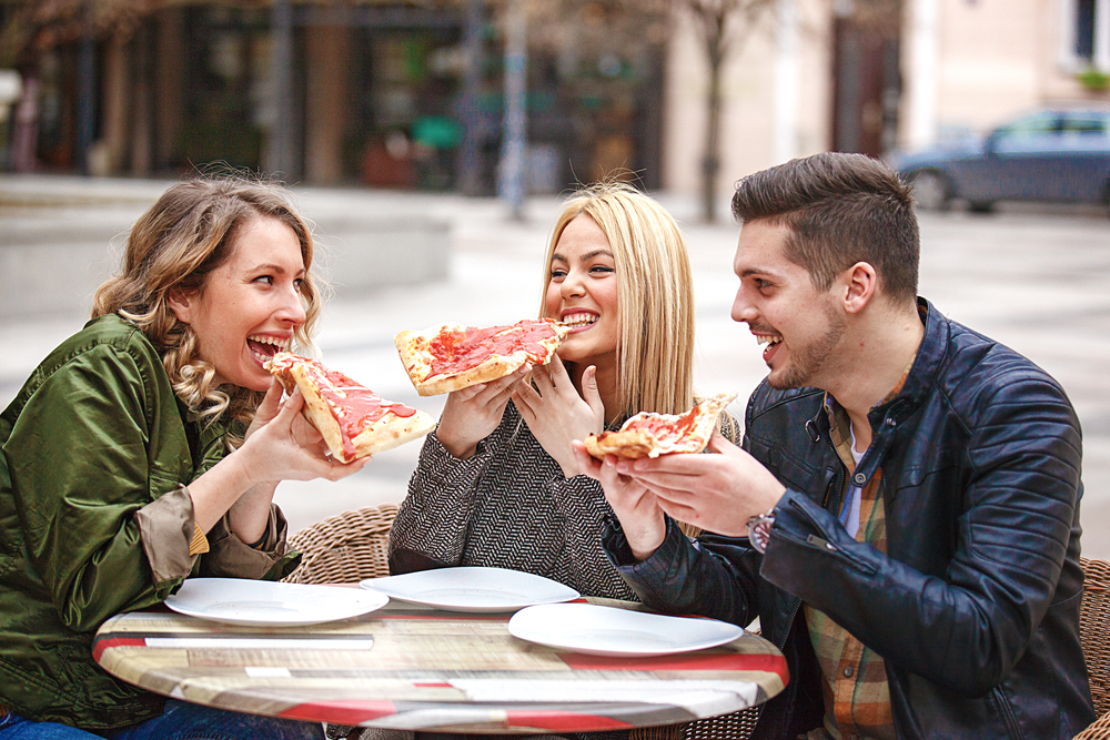 Friends eating pizza together outdoors in Starland District, Savannah GA