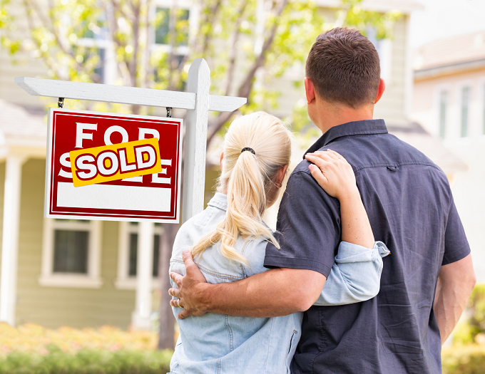 Couple in front of Sold Sign